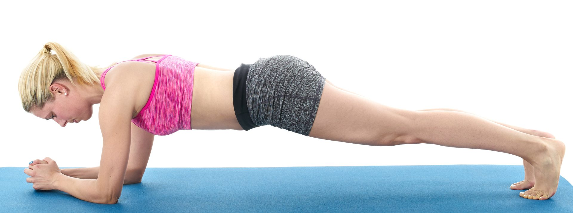 Hammersmith Physiotherapy Young woman doing full body yoga exercise on blue mat